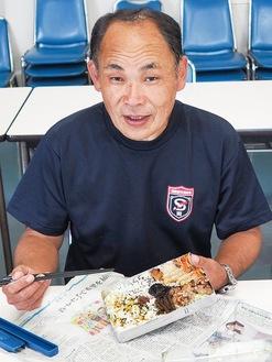 お弁当を手に笑顔を見せる門倉正道さん。弁当箱を包む新聞紙とハンカチは必需品。