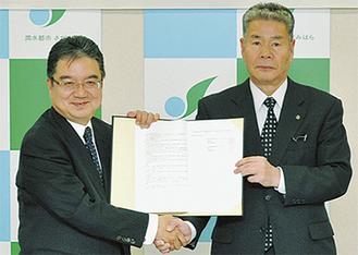 固い握手を交わす同社の杉浦役員(左)と小星副市長