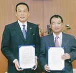 ◀今年2月、加山俊夫相模原市長と協定をかわした。右は長田代表理事