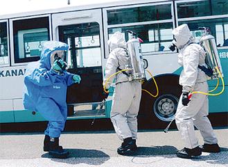 防護服を着てバスを除染