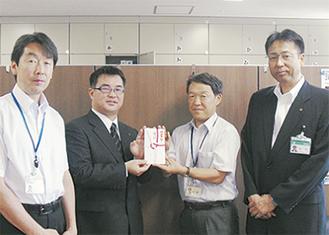 目録を手渡す佐藤マネージャー(左2番目)