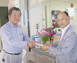 森居会長から寄付金を受け取る熊谷会長(右)