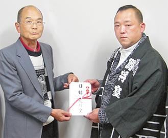 寄付金を受け取る今井会長(左)