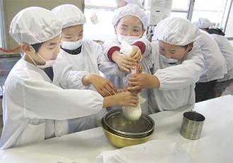 熱した大豆を絞る児童たち