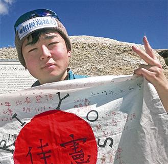 山頂で日の丸を掲げる齋藤さん