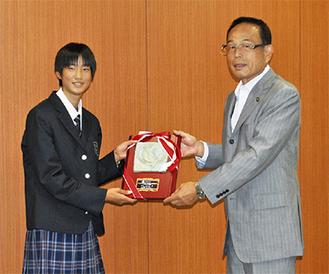 加山市長から称賛の楯を受け取る西山さん(左)