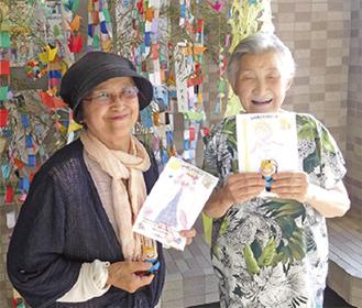 人形とカードを手にするサービス利用者(右)とボランティア