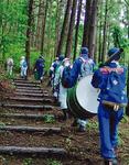 ドラム缶を担いで山道を進む消防団員ら