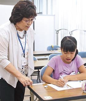 児童の様子を見ながら助言する小田さん(左)=25日