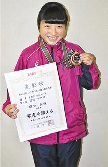 メダルと賞状を持ち喜びを表す関口さん