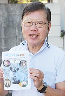 冊子を持つ小川さん