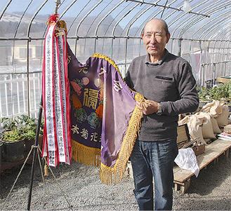 優勝旗を手にする遠藤さん=11月21日、大島の自宅で