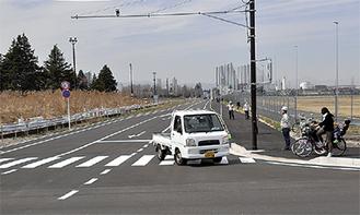 開通した東西道路を通る車両=26日正午過ぎ