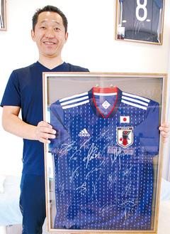選手からスタッフにプレゼントされたユニフォームを持つ久保田さん
