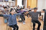 DVDを見ながら手の運動を実践する参加者=13日すすきの自治会館