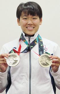 アジア大会で獲得した2つの銅メダルを持つ小堀さん=9月18日、ドルフィンクラブで
