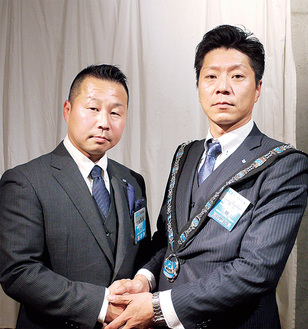 固い握手を交わす渡邉理事長(左)と佐藤次年度理事長(右)
