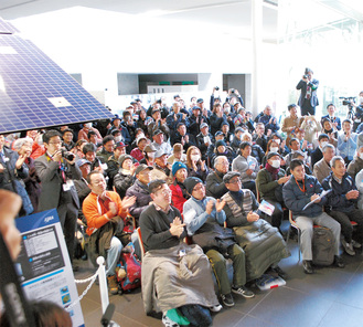 着陸達成に拍手を送るPV参加者=2月22日、博物館