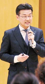 登壇する田中氏=18日