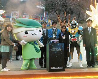 点灯式で記念撮影する関係者ら。左端は真田ぽーりんさん、右端は道本社長=3月30日、プレジャーフォレスト