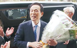 市職員や市民に見送られ、花束を抱えて謝辞を述べる加山俊夫市長=19日、市役所正面玄関前で