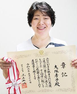 記念の看護章と章記を手に微笑む大塚さん=5月25日、相模原協同病院