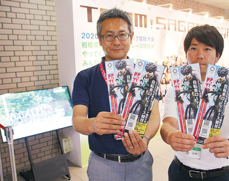 市役所ロビーで競技を紹介するパンフレットを手にする市職員。その後ろにはPRパネルが設置され、その横で動画が放映されている