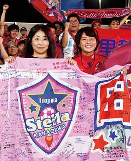 サポーターから寄せ書きを贈られ、母・友里さん(左)と笑顔を見せる田中選手
