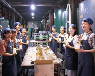 できあがった梅酒を手にする学生たち=9月6日、久保田酒造