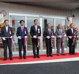 新棟入口でテープカットする橋元代表取締役(左から3番目)、本村賢太郎市長(同4番目)ら関係者=9月5日