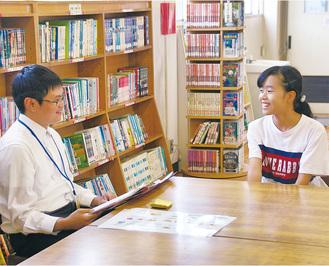 自分の誕生日や好きなものなどを英語でALT(左)に伝える6年生児童=10月3日、橋本小学校図書室で