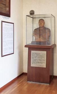 体育館にある小菅千代市氏の胸像(右)。左に同館の成り立ちを記した案内板がある