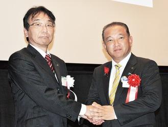 締結式での署名を終え、手を組む本村市長(右)と國中所長=1日、国立映画アーカイブ相模原分館