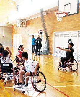 車いすバスケットボールを体験し、根木さん(右)からパスを受ける児童ら=6日