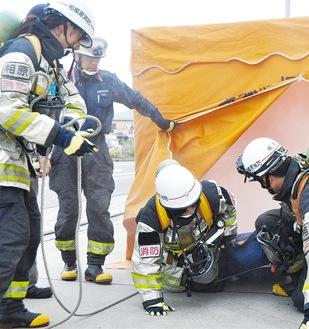 救助隊員の指導のもと救助体験を行う参加者ら