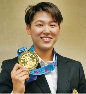 国民体育大会で獲得した金メダルを手に微笑む小堀さん=11月21日、市役所