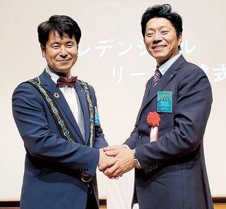 笑顔で固い握手を交わす、佐藤理事長(右)と高橋次年度理事長