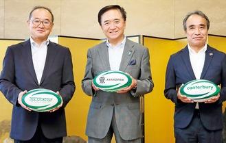 寄贈したラグビーボールを手に笑顔の梶野社長(左)=8月28日、県庁