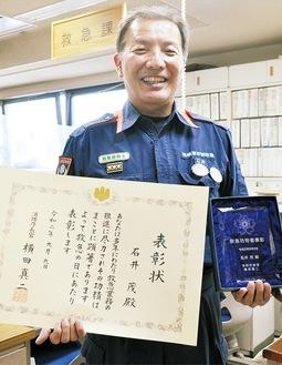 職場で賞状を手に笑顔の石井さん