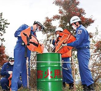 設置したドラム缶に防火用水を入れる消防団員