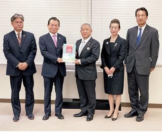 設立30周年記念誌を本村賢太郎市長に渡す板橋理事長(左から2番目)=1月6日