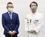目録を受け取る井關病院長(右)と江成代表