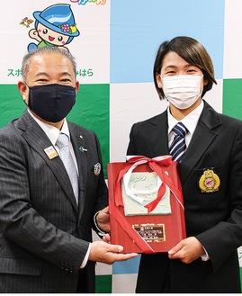 「称讃の楯」を受け取る小堀さん(右)と、贈呈した本村市長=2月19日、市役所