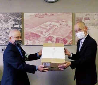 平栗文夫津久井交通安全協会会長(左)から古屋校長へ啓発グッズが贈呈された