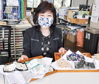 手作りマスクの一例を見せる小山会長