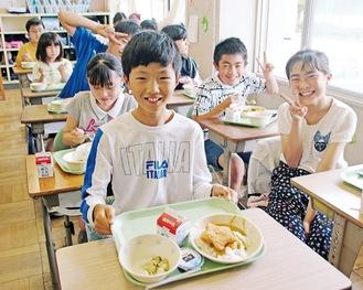 感染対策のため食事中の私語は慎みながらも、年に1度の特別な献立に笑顔の児童たち=11日
