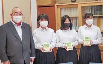 左から高橋社長と寄贈された本を手にする中央中学校の藤原さくらさん、池内綾香さん、横山瞳さん