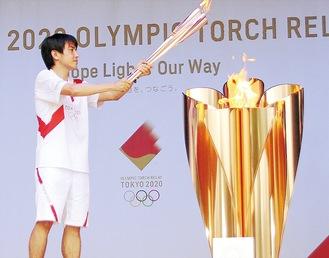 代替イベント2日目の最終ランナーとして聖火皿に点火させた、市内在住でJAXA勤務の月崎さん=6月29日、橋本公園