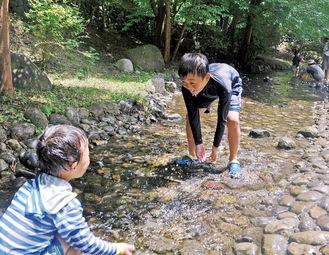 同公園内を流れる小川で水をかけあう子どもたち=7月24日