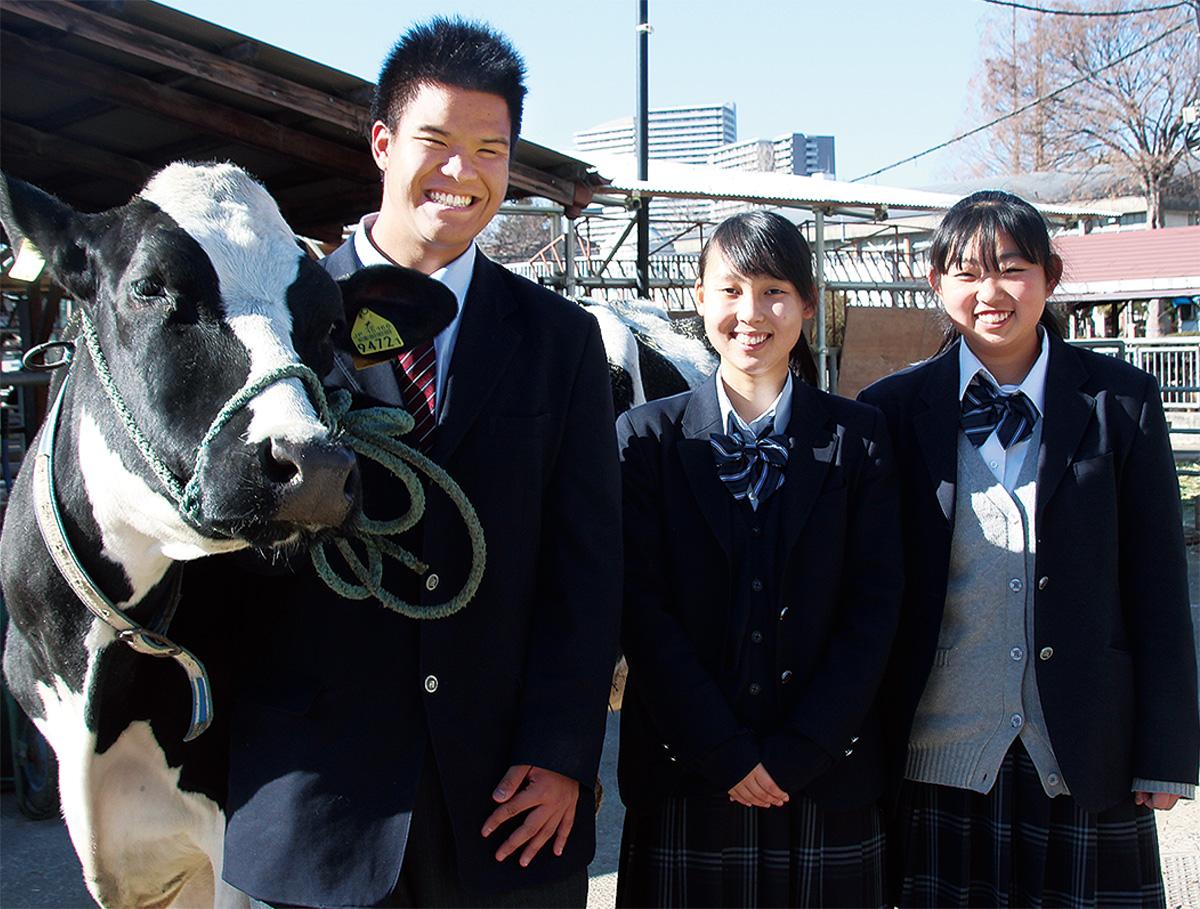 相原高校で、飼育する乳牛と一緒に撮影。左から角田さん、塗井さん、吉川さん=1月19日